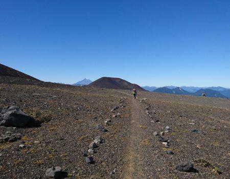 Largo sendero con persona al fondo y vista al volcán Lanin