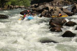 Grupo de personas en una balsa de rafting bajando el río