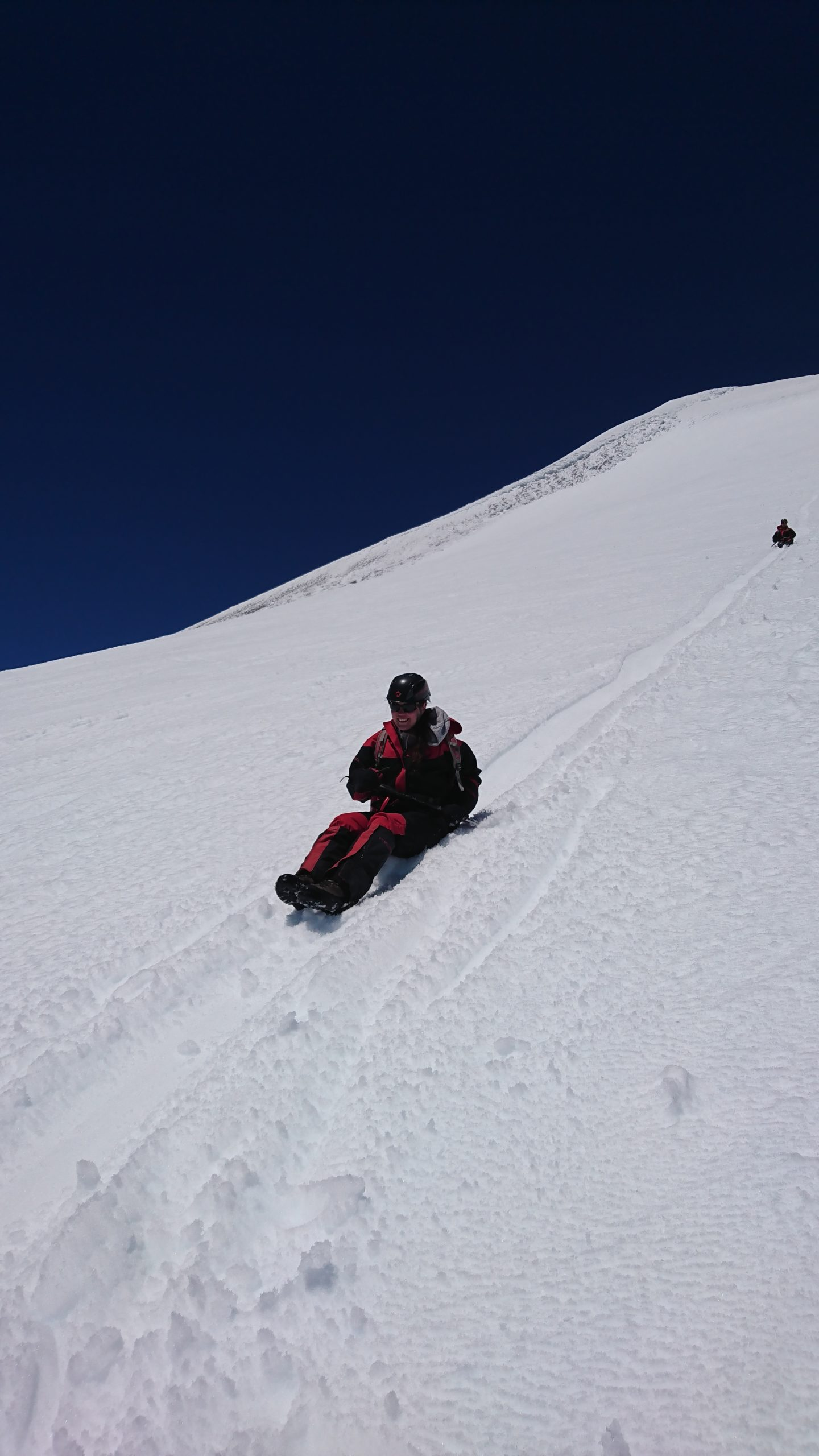 Persona deslizando sentada en la nieve